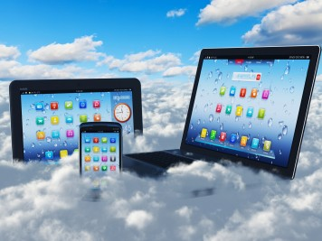 Creative cloud computing concept: modern laptop notebook, tablet computer PC and black glossy touchscreen smartphone in the blue sky with clouds